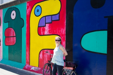 Caitlin in front of the Berlin wall with graffiti.